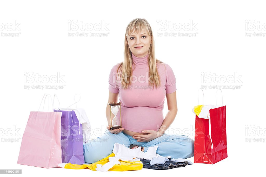 Happy pregnant woman with shopping bags and hour glass royalty-free stock photo