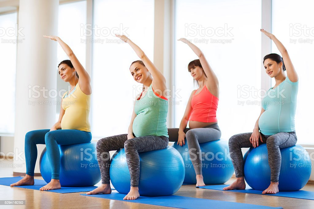 happy pregnant women exercising on fitball in gym stock photo