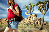 Side view of a smiling pregnant lady in casual clothing with a backpack on a hike through Joshua Tree National Park enjoying her exercise.  Her face is only partially visible, from the smile down.  Horizontal.