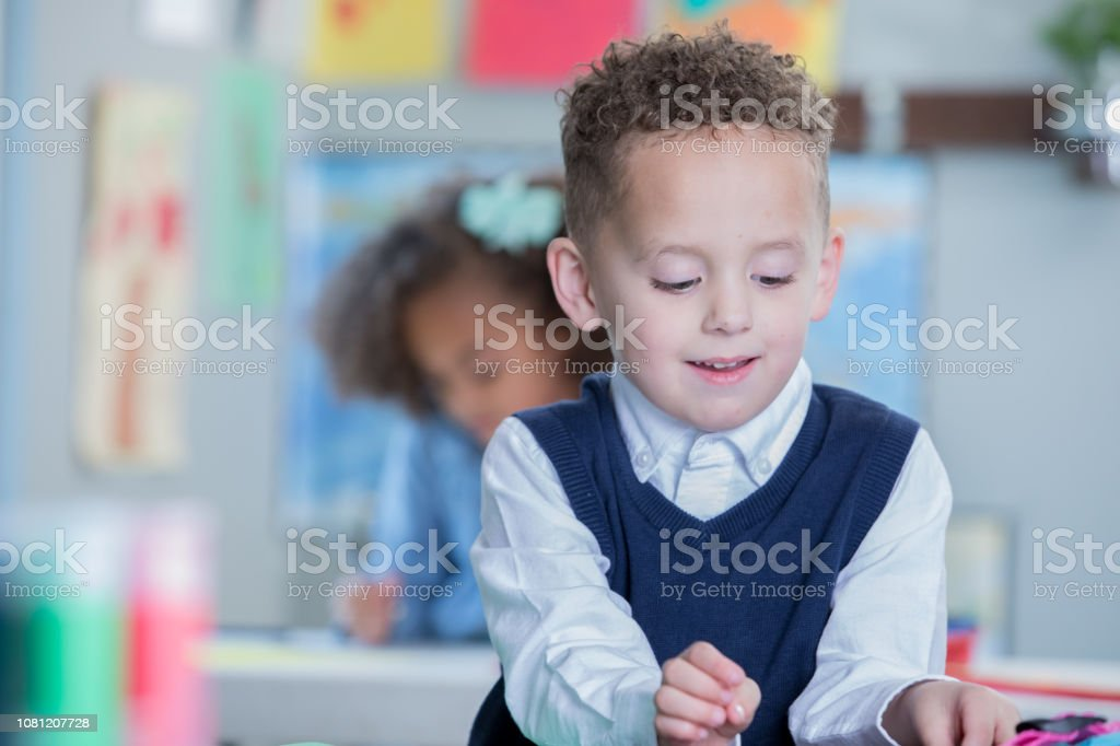 Happy preschool age mixed race little boy with curly hair smiles...