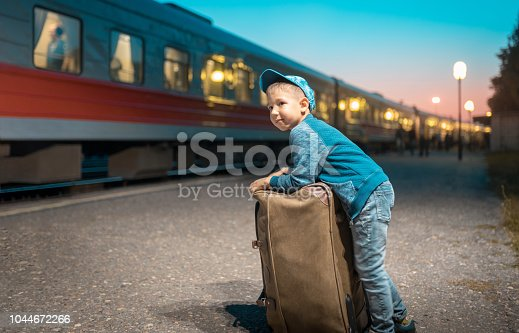 The elementary age boy is standing with his suitcase next to a train. He is leaning to his luggage and looking away. Shooting at the rail station