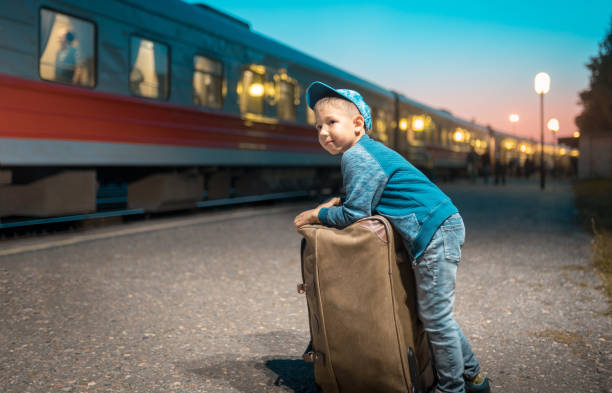 Happy Preschool Boy Is Waiting for Depart in Travel The elementary age boy is standing with his suitcase next to a train. He is leaning to his luggage and looking away. Shooting at the rail station depart stock pictures, royalty-free photos & images