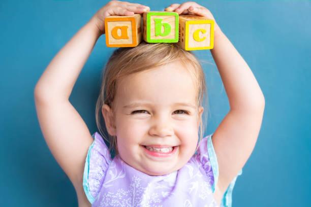 glückliches vorschulkind lernen abc mit spielzeugblöcken. zurück zur schule. - 2 3 jahre stock-fotos und bilder