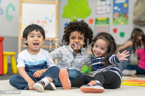 Portrait of three preschool age children. The multi-ethnic group of friends are embracing and laughing. The students are sitting together on the floor in their classroom. There are other school children playing in the background.