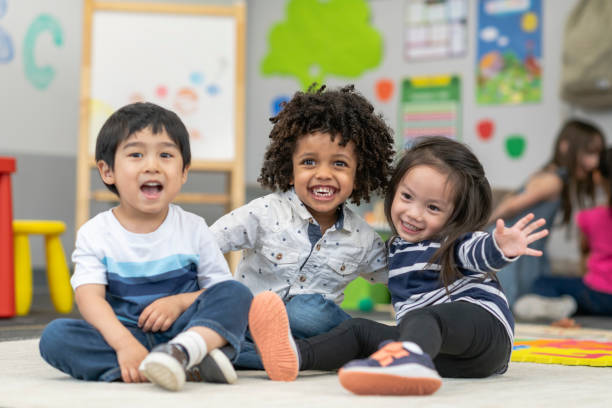Happy Preschool Friends Portrait of three preschool age children. The multi-ethnic group of friends are embracing and laughing. The students are sitting together on the floor in their classroom. There are other school children playing in the background. preschool age stock pictures, royalty-free photos & images
