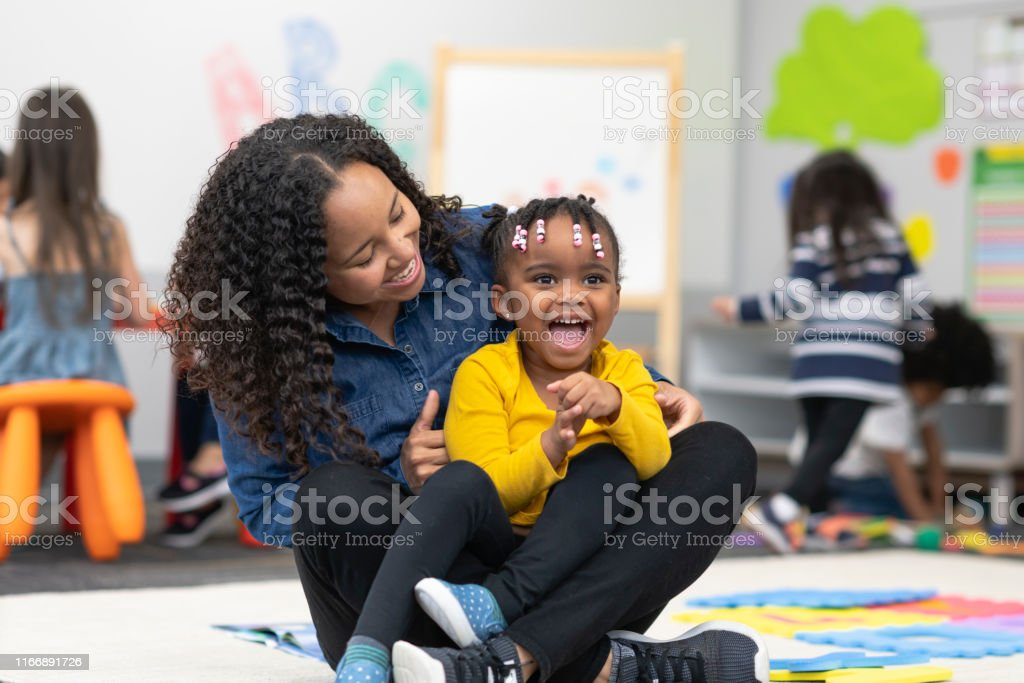 A cute preschool girl sits on the lap of her mixed-race teacher. The...