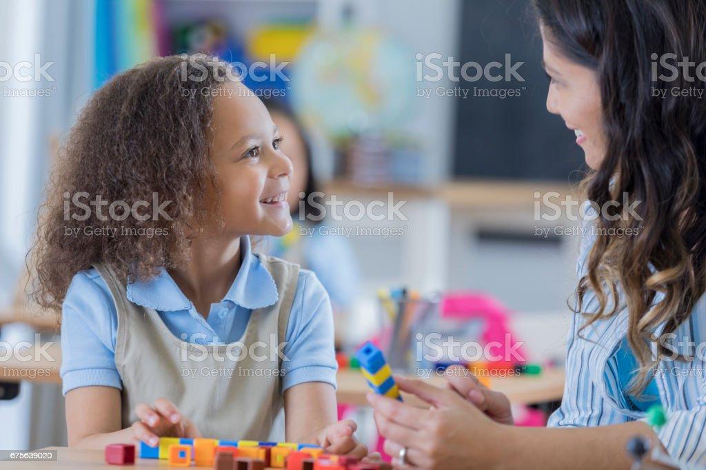 Happy preschool student talks with teacher royalty-free stock photo
