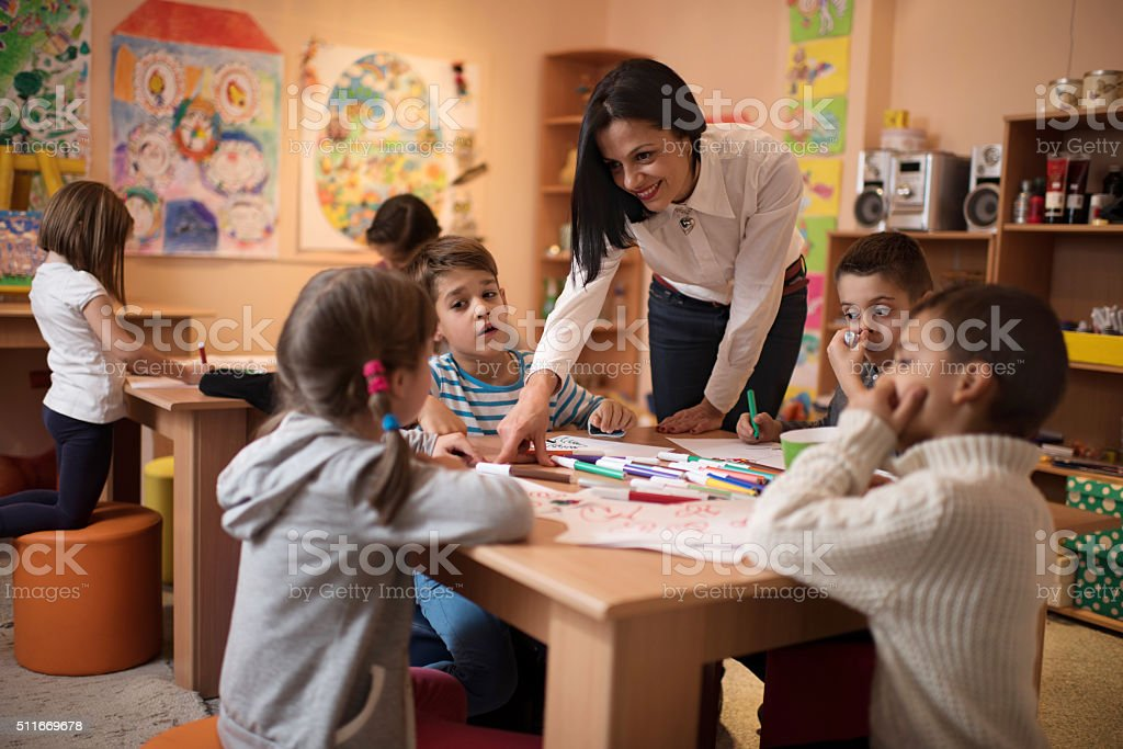 Happy preschool teacher assisting children with their drawings. stock photo