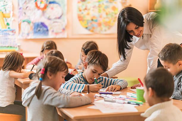 feliz preescolar profesor ayudando a niños con sus ilustraciones. - clase de arte fotografías e imágenes de stock