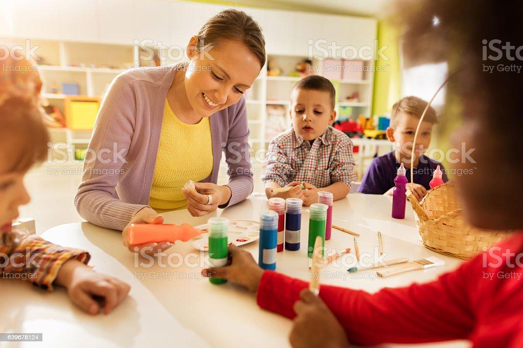 Happy preschool teacher coloring with kids in kindergarten. stock photo