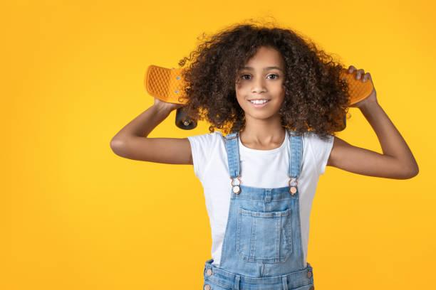 feliz pré-adolescente segurando skate no ombro isolado em fundo amarelo - pré adolescente - fotografias e filmes do acervo