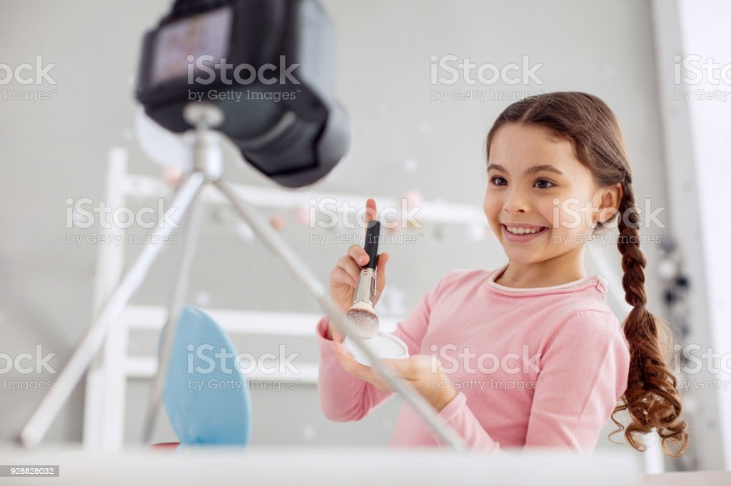 Happy pre-teen girl testing powder for her tutorial stock photo