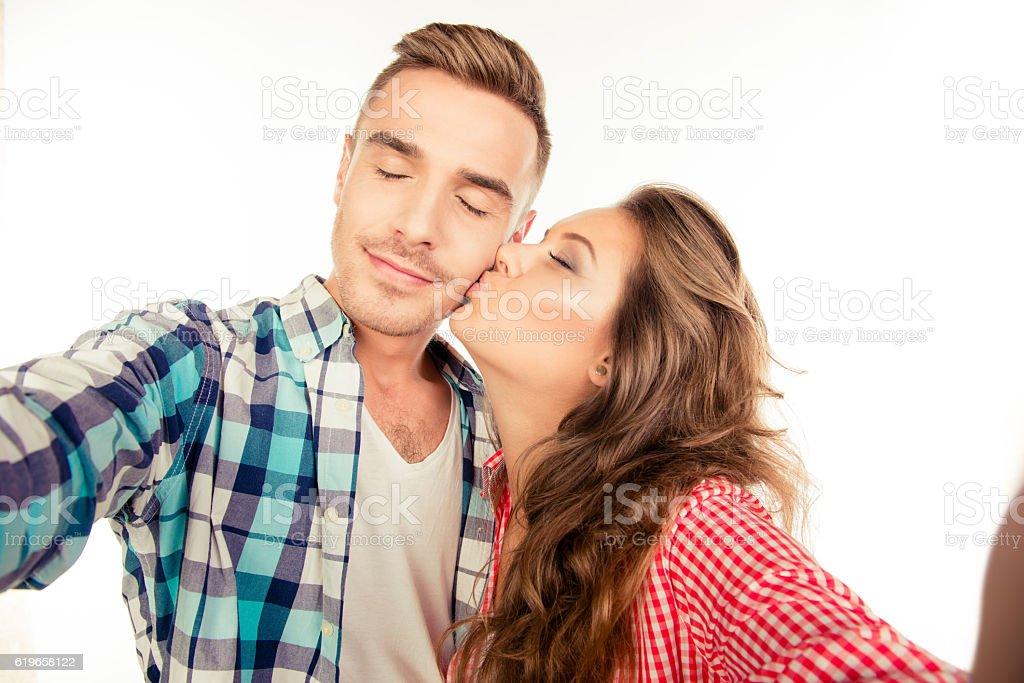 Happy pretty girl kissing her boyfriend making selfie - foto de acervo