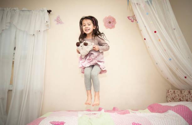 glücklich hübsches kleines mädchen springen auf ihrem bett - mädchenraum vorhänge stock-fotos und bilder