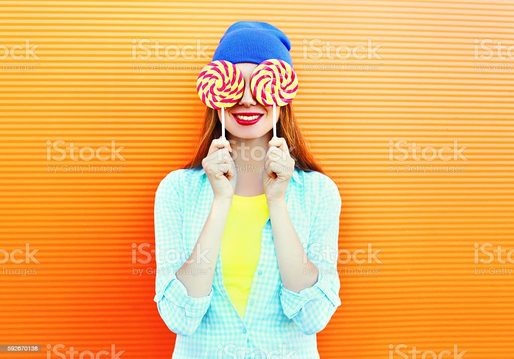 happy pretty smiling woman and lollipop having fun over colorful stock photo