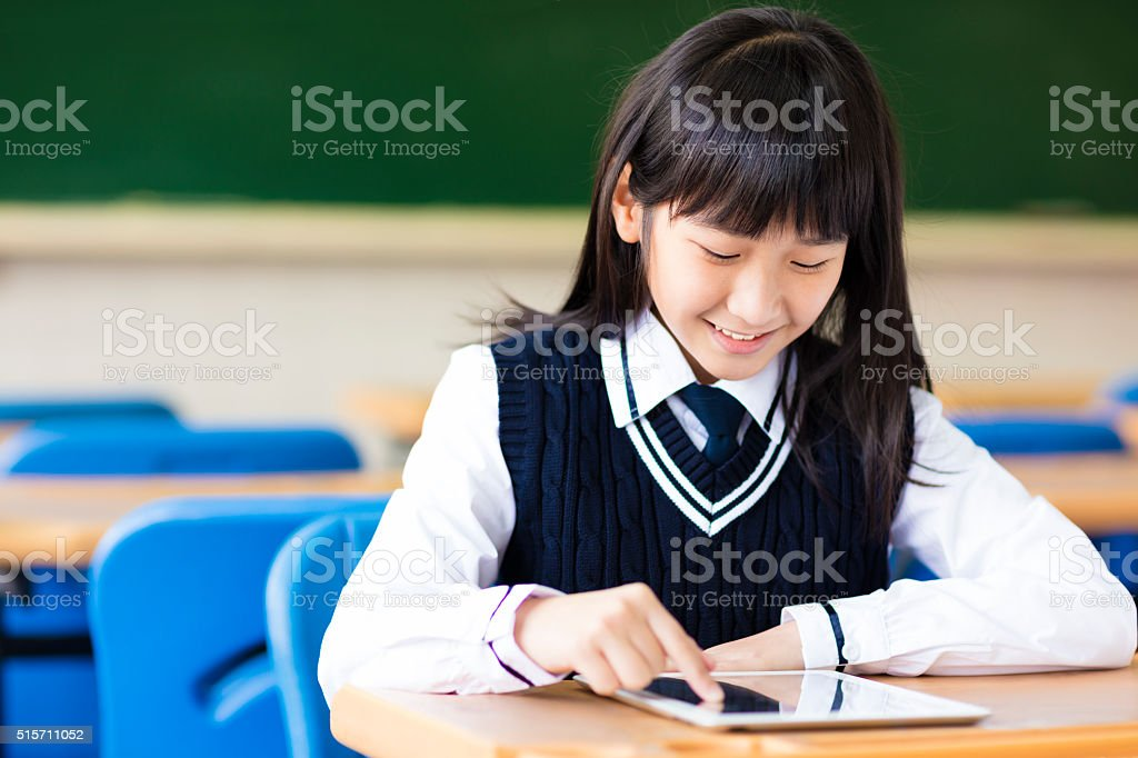 happy pretty  student girl with tablet  in classroom stock photo