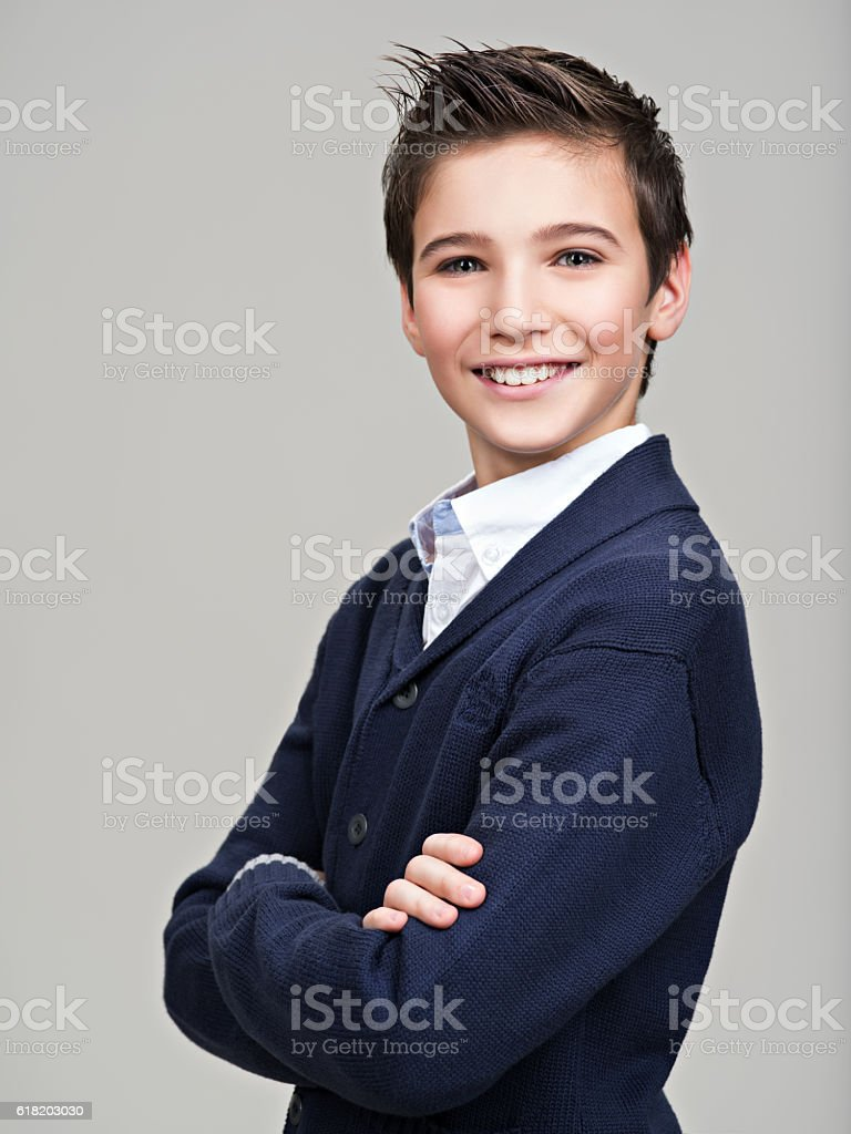Happy pretty teenage boy posing at studio stock photo
