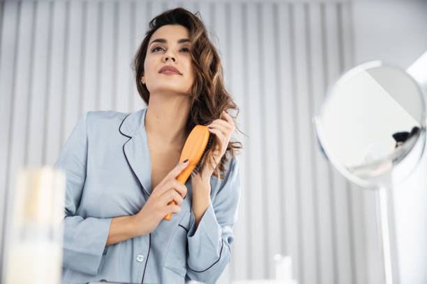 Happy pretty woman brushing healthy hair at home stock photo