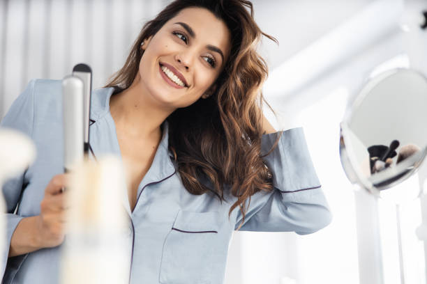 Happy pretty woman holding curling iron at home stock photo