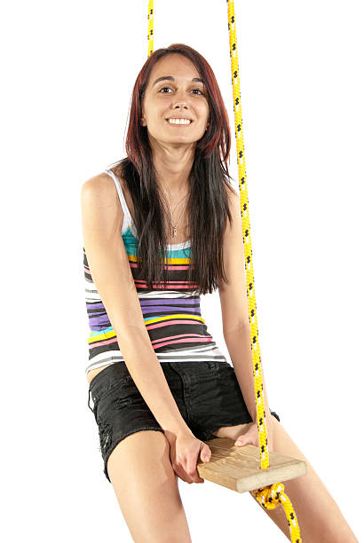 Happy pretty young girl swinging on a swing stock photo
