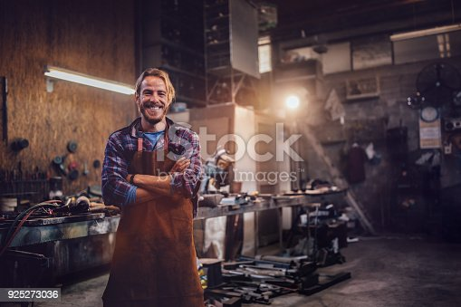 istock Happy professional craftsman standing in workshop with tools 925273036