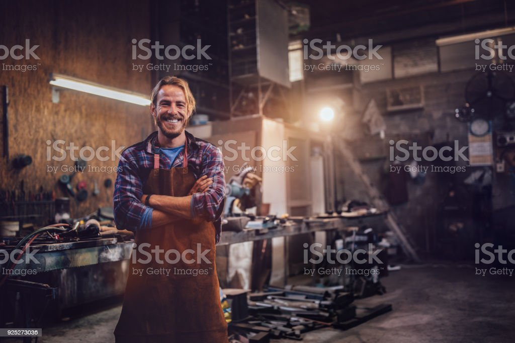 Happy professional craftsman standing in workshop with tools stock photo