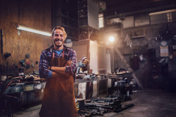 Happy professional craftsman standing in workshop with tools Portrait of smiling mechanic standing in garage workshop with professional equipment metalwork stock pictures, royalty-free photos & images