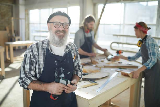 Egovolle, professionelle ältere Zimmerangestellerin in Mützenhut und Brille, die im Fabrikladen stehen und Akku-Schrauber halten, während sie auf die Kamera schauen – Foto