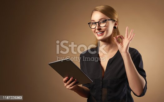 Happy professional girl wearing glasses and holding tablet on brown background