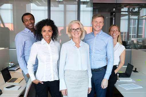 istock Happy professional team with old female business leader posing together 1146468404