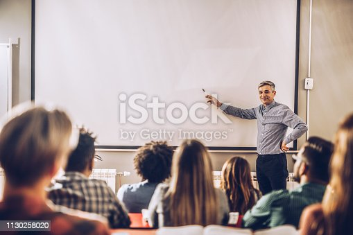 Happy male teacher giving a lecture to large group of students on visual screen in the classroom. Copy space.