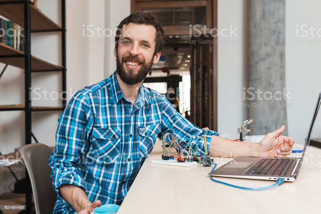 Happy programmer smiling at camera near laptop Lizenzfreies stock-foto