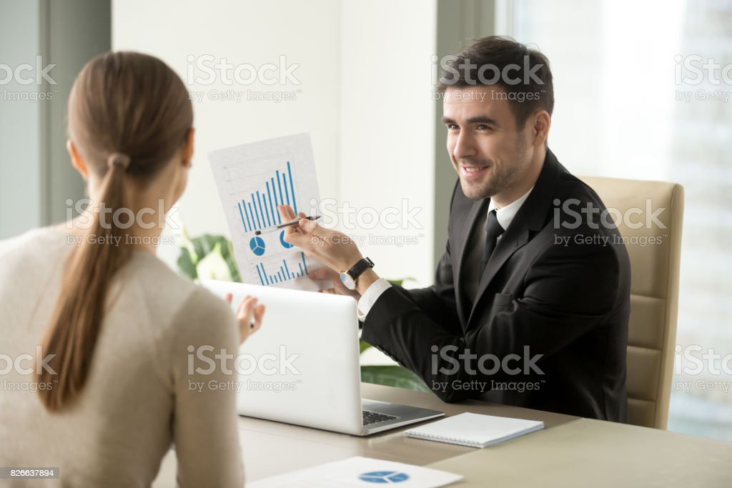 Happy project manager showing financial report, rising stats, growing graphs stock photo
