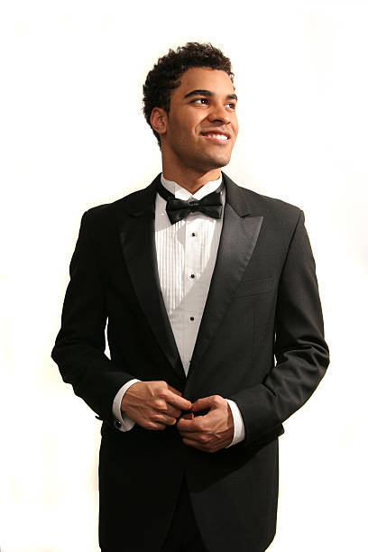 Happy prom date Young minority guy in a tuxedo isolated on white tuxedo stock pictures, royalty-free photos & images