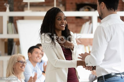 istock Happy proud black female employee get rewarded handshake caucasian boss 1164377567