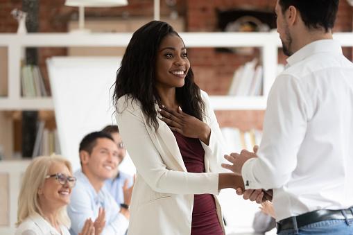 istock Happy proud black female employee get rewarded handshake caucasian boss 1164377567