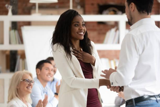 glücklich stolze schwarze mitarbeiterin erhalten handshake caucasian chef belohnt - gestikulieren stock-fotos und bilder