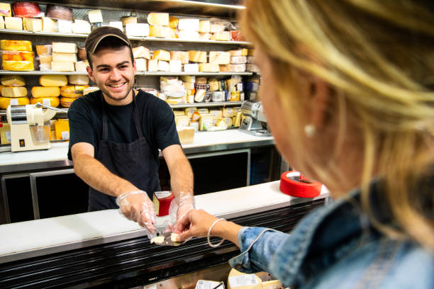 A happy, proud young specialty cheese seller giving a customer a sample of cheese. stock photo