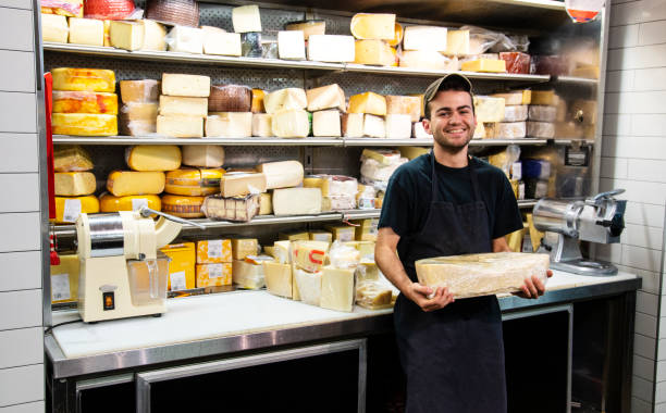 A happy, proud young specialty cheese seller stock photo