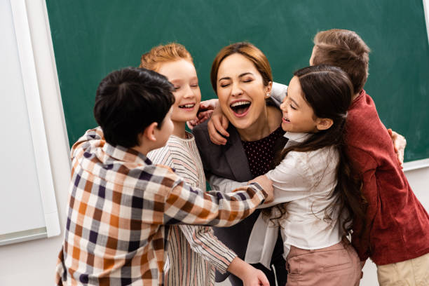 Glückliche Schüler umarmten Lehrer vor Tafel im Klassenzimmer – Foto
