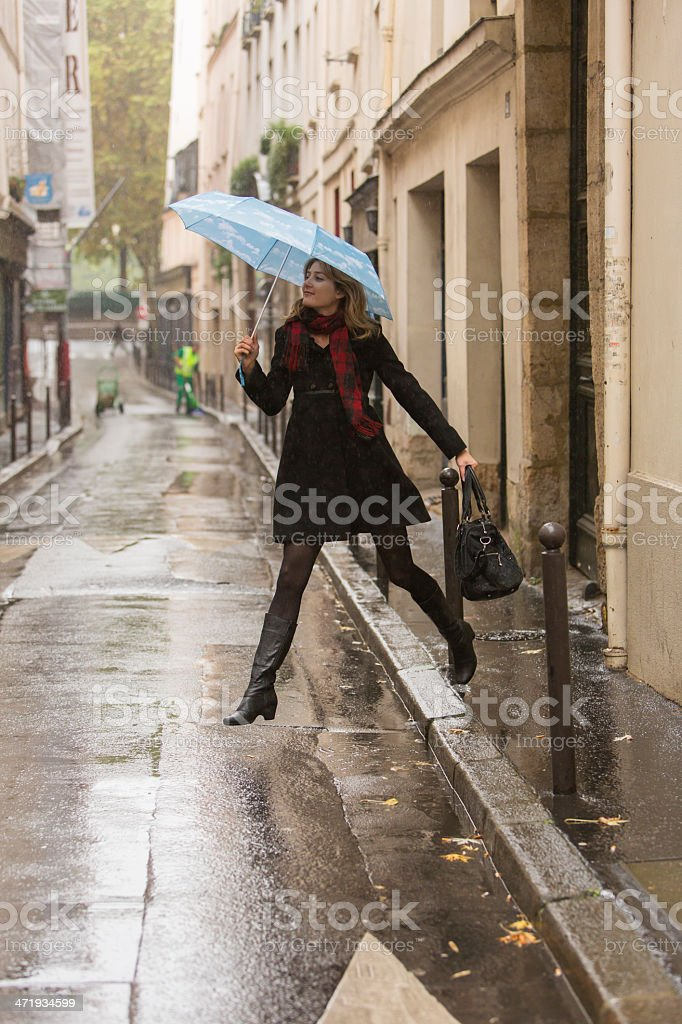Happy young woman jumping in the rain in Paris