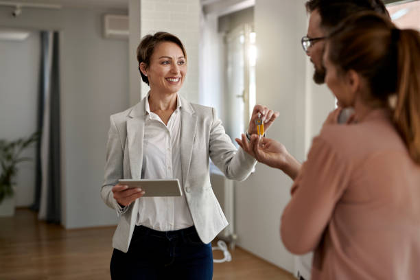 Happy real estate agent giving to a couple keys of their new home. stock photo