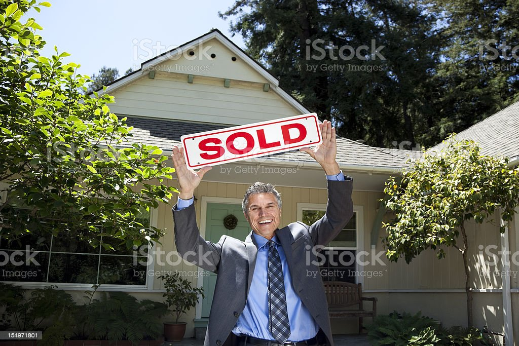 happy real estate agent holding up SOLD sign