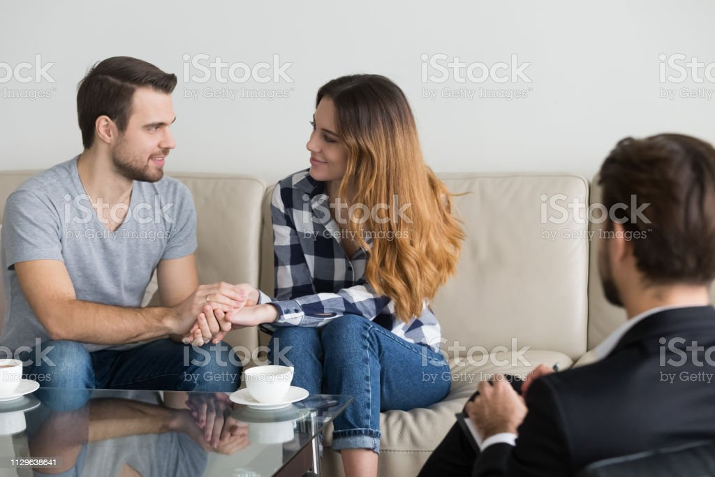 Happy reconciled couple holding hands satisfied with family therapy session
