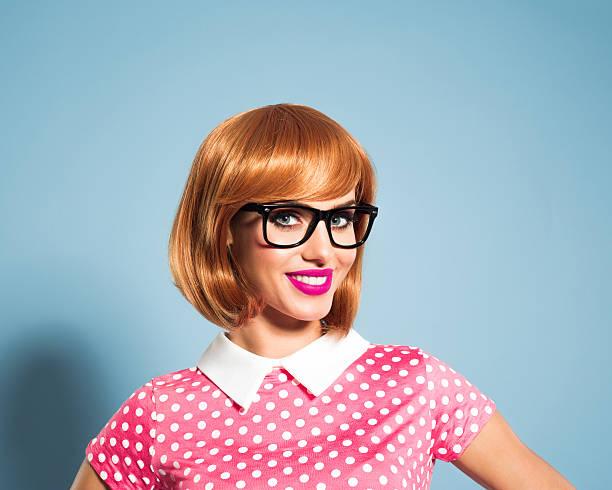 glücklich rotes haar junge frau mit kleid mit pünktchenmuster - moderne 50er jahre mode stock-fotos und bilder