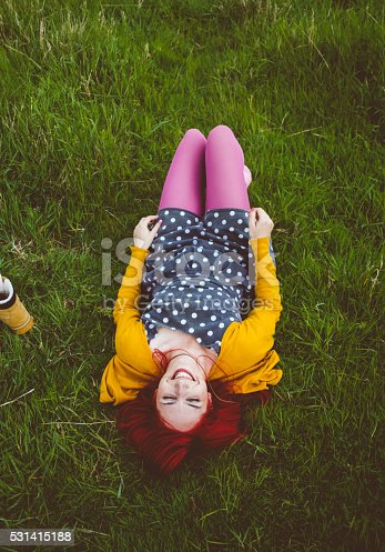 833314292istockphoto Happy red haired woman resting in the field 531415188