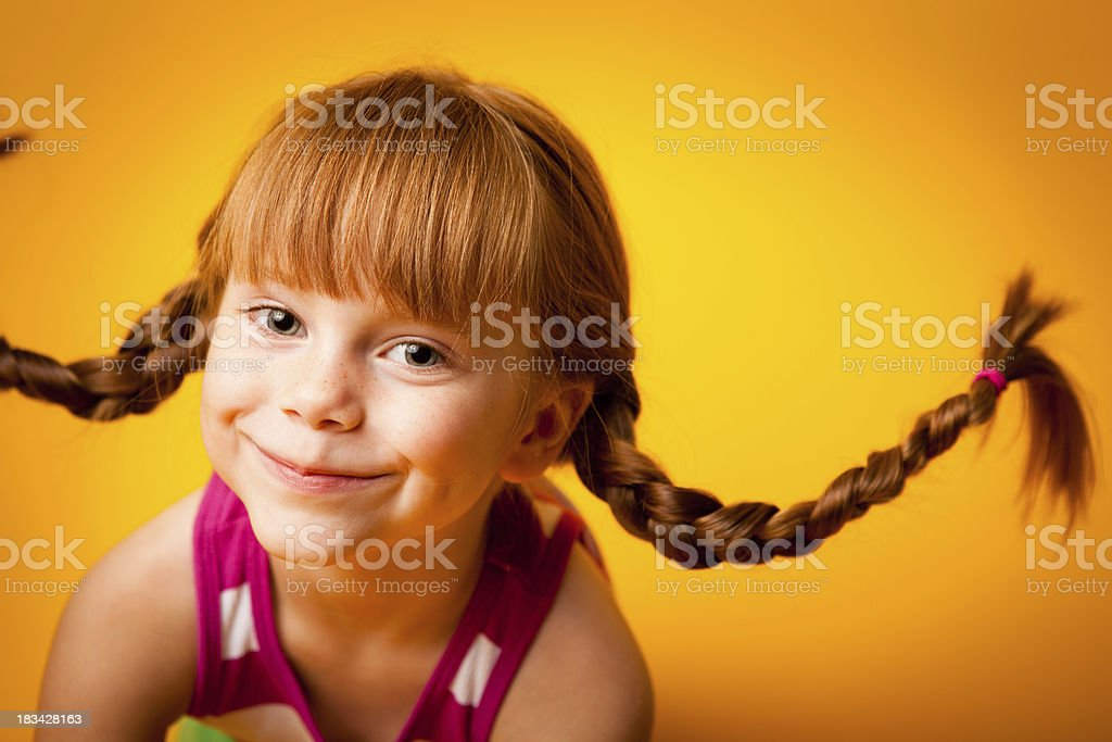 Happy, Red-Haired Girl with Upward Braids and a Smile royalty-free stock photo