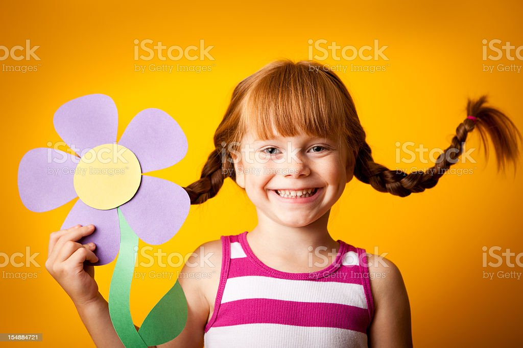 Happy Red-Haired Girl with Upward Braids Holding Paper Flower stock photo