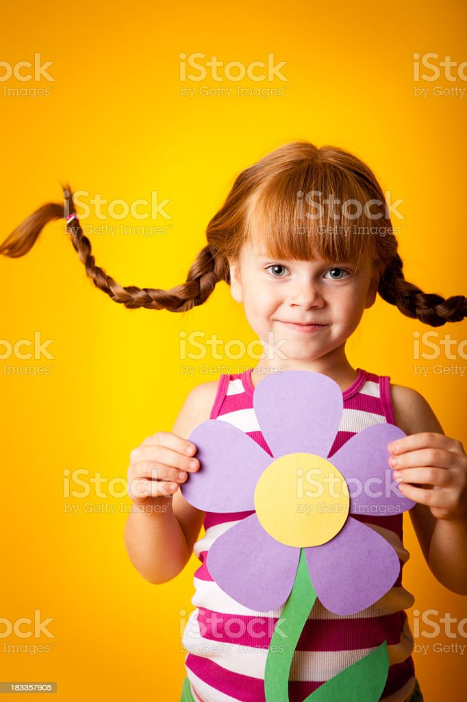 Happy Red-Haired Girl with Upward Braids Holding Paper Flower royalty-free stock photo
