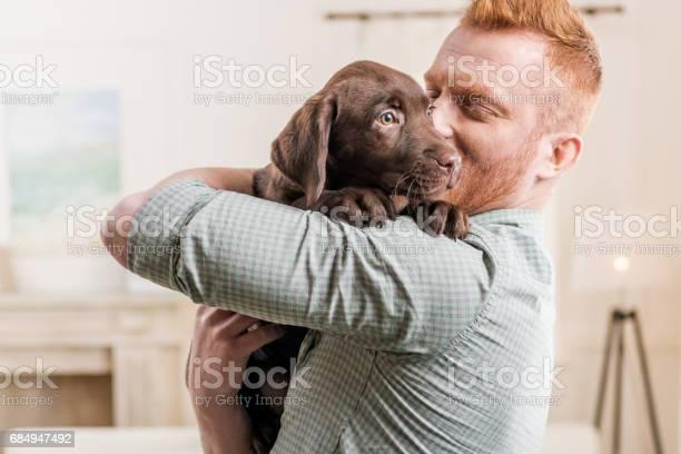 Happy redhead man holding labrador retriever puppy at home picture id684947492?b=1&k=6&m=684947492&s=612x612&h=0drudzmzgpxpocu3ucoyijy9bre33xzqgufxdj0 g18=